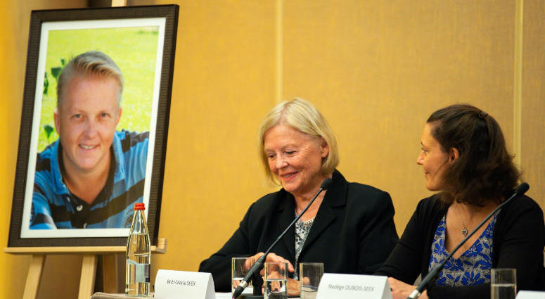 Nadege Dubois-Seex (right) at a Paris press conference on May 21 alongside a portrait of her late husband, Jonathan Seex, and his mother Britt-Marie Seex (center).