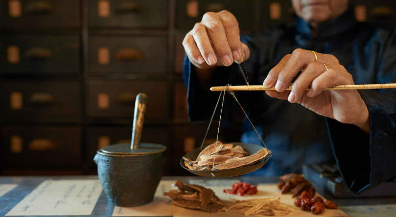 A man measures ingredients in traditional Asian apothecary.