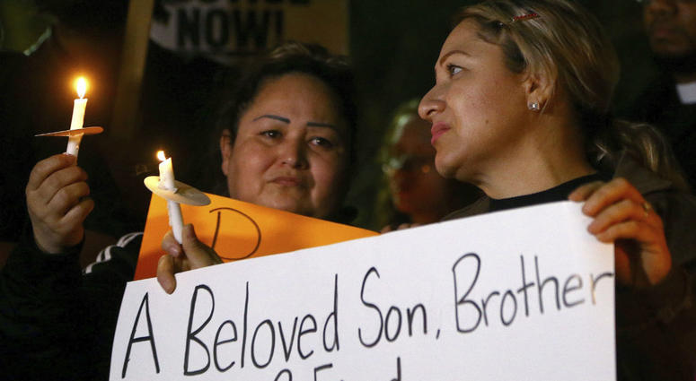 Sandra Gonzalez, left, mother of slain 14-year-old boy shot by Tempe Police, joins protesters in front of police headquarters Thursday, Jan. 17, 2019, in Tempe, Ariz.