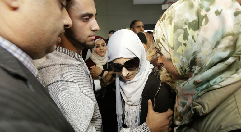 Shaima Swileh, center, stands with her husband Ali Hassan, second from left, after Swileh arrived at San Francisco International Airport in San Francisco, Wednesday, Dec. 19, 2018.