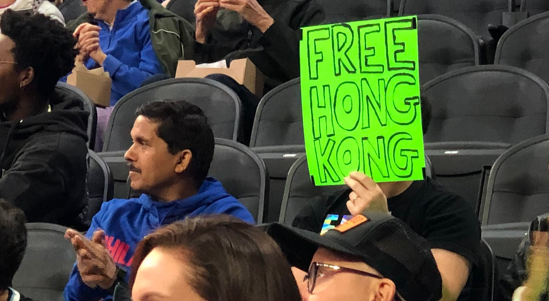 """Sam Wachs is shown holding a sign reading """"Free Hong Kong."""""""