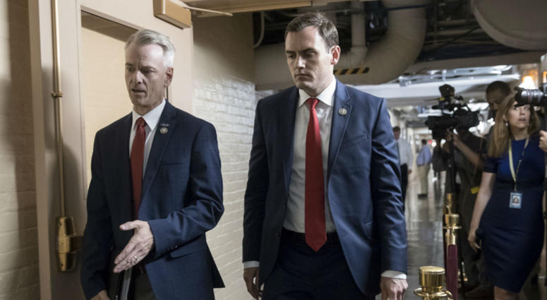 Rep. Steve Russell, R-Okla., left, and Rep. Mike Gallagher, R-Wis., walk to a closed-door meeting with House Republicans seeking more information about compromise legislation on immigration, at the Capitol in Washington, Thursday, June 21, 2018.