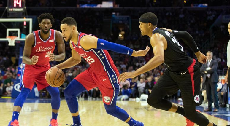 Philadelphia 76ers guard Ben Simmons dribbles past LA Clippers forward Tobias Harris in front of center Joel Embiid  during the third quarter at Wells Fargo Center on Nov 1, 2018.