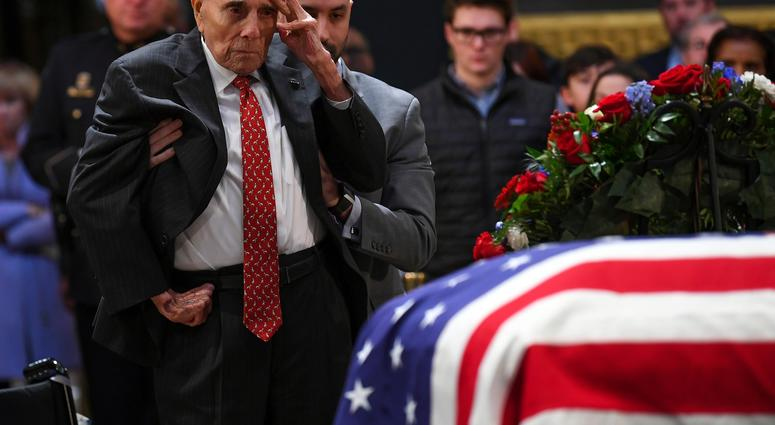 Dec 4, 2018; Washington, DC, U.S.A; Former Sen. Bob Dole salutes the casket of President George H.W. Bush who lies in state at the U.S. Capitol Rotunda.