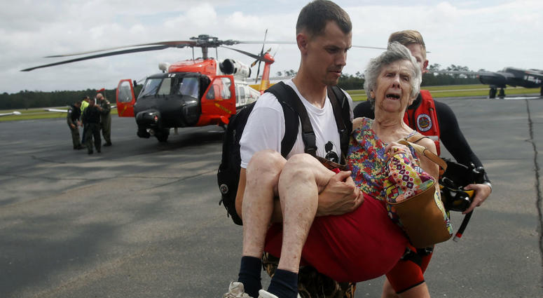 An unidentified family member carries Ruth Brady to safety at the Wilmington airport in Wilmington, N.C., Monday, Sept. 17, 2018.