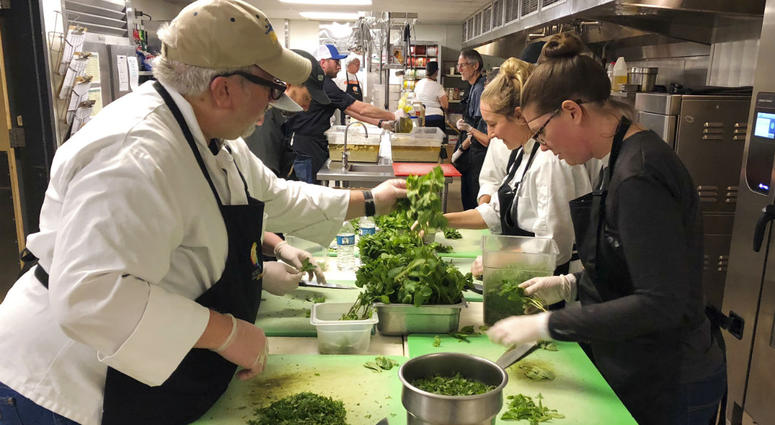Michael Reining, left, and Chelsea Meddings, right, chop mint in preparation for a community Thanksgiving meal for survivors of the deadly Camp Fire in Northern California, on the campus of California State University, in Chico, Calif.