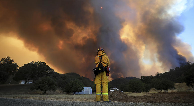 A tower of smoke pours from Cow Mountain as Burney, California firefighter Bob May keeps a watch on surrounding vegetation for spot fires during a wildfire off Scotts Valley Road, Thursday, Aug. 2, 2018, near Lakeport, Calif.