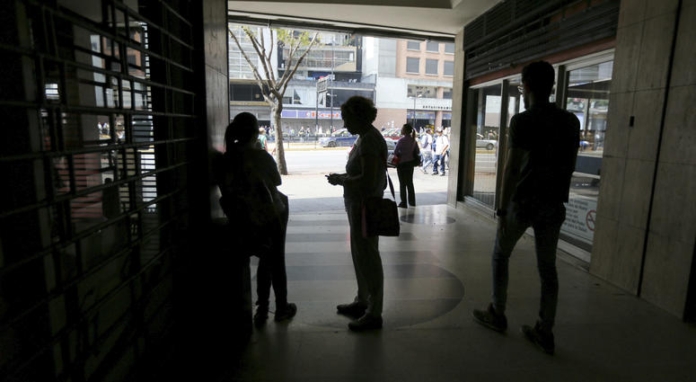 People wait inside a darkened office building during a power outage in Caracas, Venezuela, Monday, March 25, 2019.