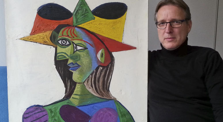 """This image released on Tuesday March 26, 2019 by Arthur Brand, shows Dutch art detective Arthur Brand with """"Buste de Femme"""", a recovered Picasso painting. The painting was stolen from a wealthy Saudi's yacht 20 years ago."""