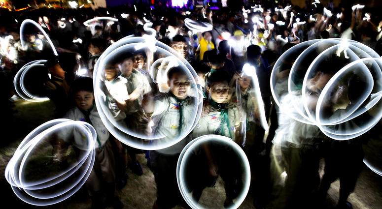 Philippine Boy Scouts play with their flashlights at the countdown for the 12th Earth Hour event Saturday, March 30, 2019 in suburban Makati city east of Manila, Philippines. Earth Hour is the symbolic switching off of the lights for one hour to help mini