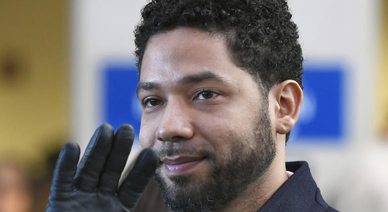 FILE - In this March 26, 2019, file photo, actor Jussie Smollett smiles and waves to supporters before leaving Cook County Court after his charges were dropped in Chicago. A deadline is looming for Smollett to pay over $130,000 to Chicago to cover part of
