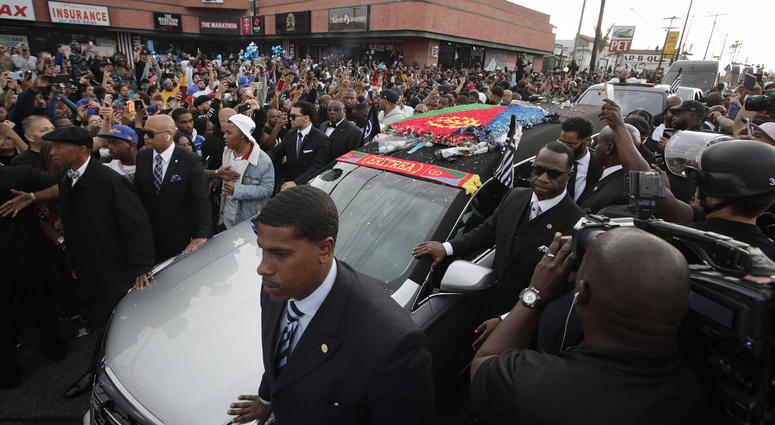 People watch as a hearse carrying the casket of slain rapper Nipsey Hussle passes Hussle's clothing store The Marathon, Thursday, April 11, 2019, in Los Angeles. Hussle's casket, draped in the flag of his father's native country, Eritrea in East Africa, e