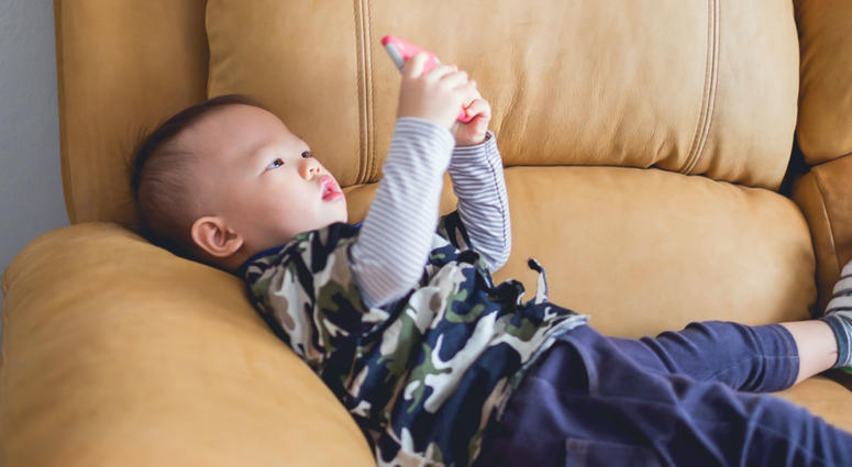 1 year old baby boy child sitting on sofa watching a video from smart phone.