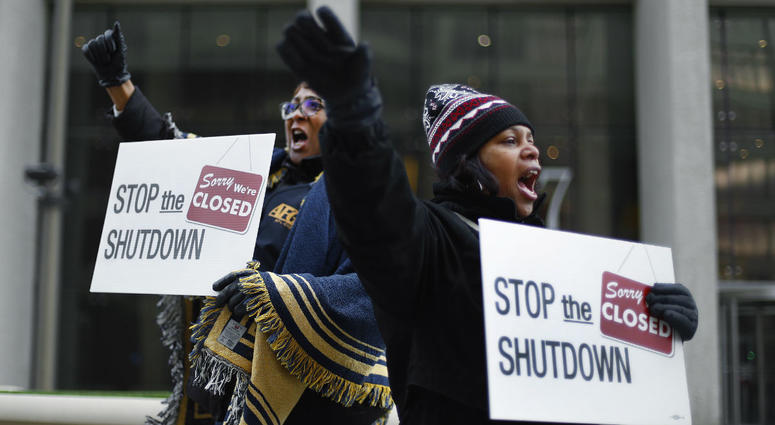 In this Jan. 10, 2019 file photo Cheryl Monroe, right, a Food and Drug Administration employee, and Bertrice Sanders, a Social Security Administration employee, rally to call for an end to the partial government shutdown in Detroit.