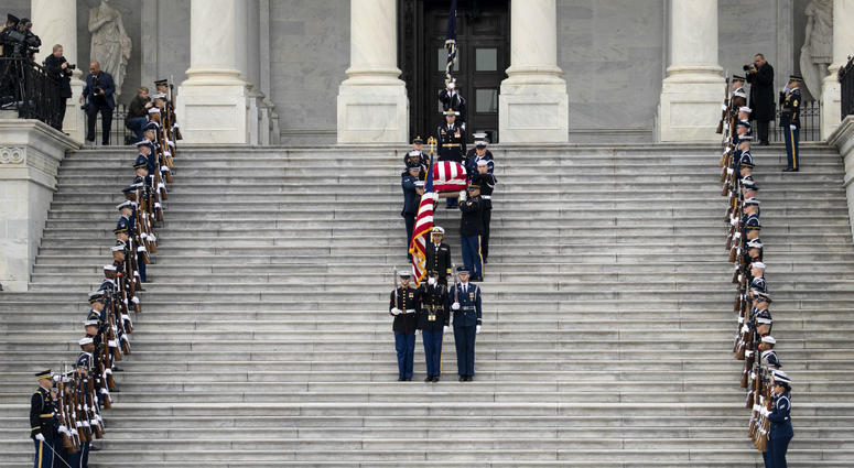 A U.S. military honor guard carries the flag-draped casket of the late former President George H.W. Bush down the steps of the U.S. Capitol, December 5, 2018 in Washington, DC.