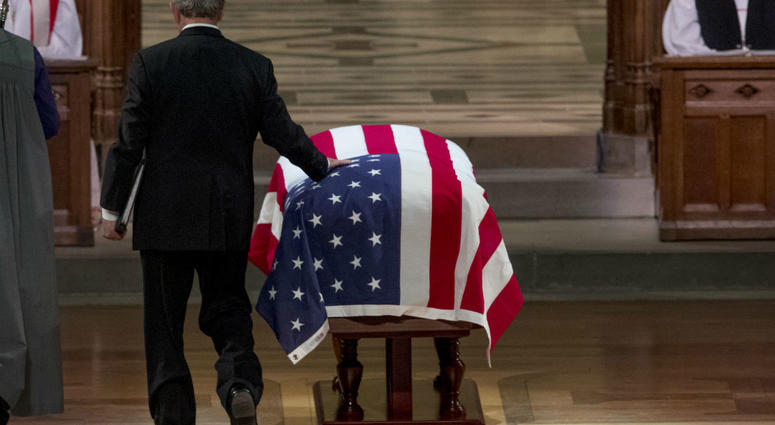 Former President George Bush touches the flag-draped casket of his father, former President George H.W. Bush, as he prepares to speak during his State Funeral at the National Cathedral, December 5, 2018 in Washington, DC.