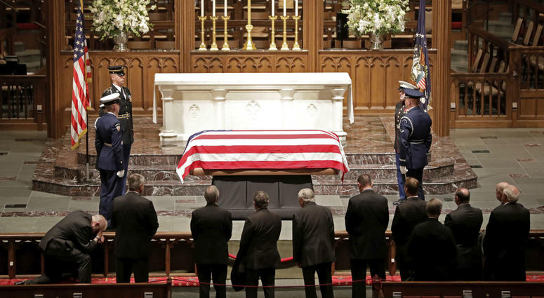 Visitors pay their respects to the flag-draped casket of former President George H.W. Bush at St. Martin's Episcopal Church Wednesday, Dec. 5, 2018, in Houston.