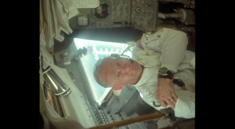 Buzz in the LM during its checkout en route to the Moon. He is on the left side of the cabin and is placing a pair of sunglasses in his jacket's arm pocket.