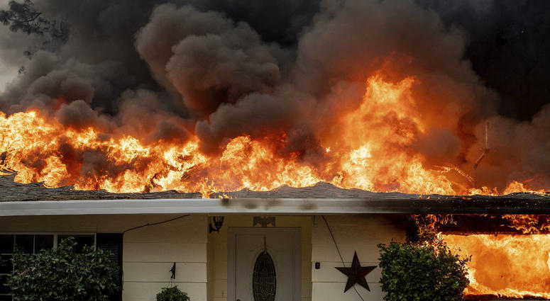 Flames consume a home as the Camp Fire tears through Paradise, Calif., on Thursday, Nov. 8, 2018.