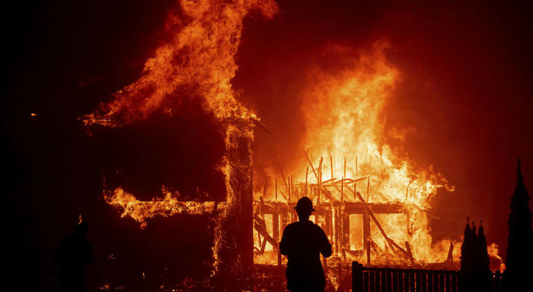 In this Thursday, Nov. 8, 2018 file photo, a home burns as the Camp Fire rages through Paradise, Calif. Authorities say the fire is 95 percent contained Thursday, Nov. 22.