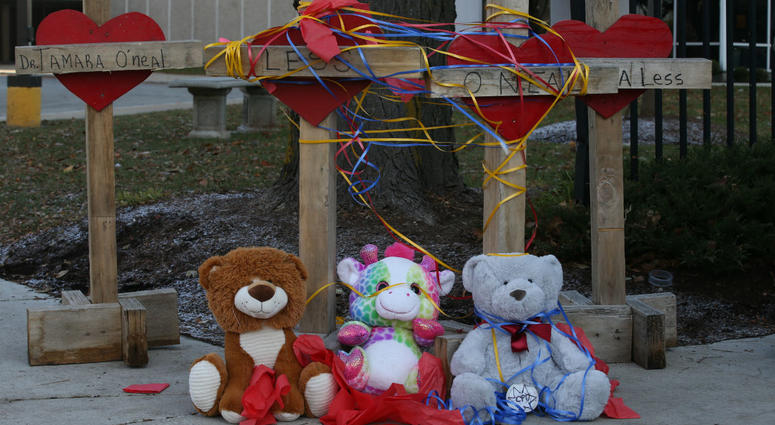 Items are left at a memorial at Mercy Hospital, Tuesday, Nov. 20, 2018, in Chicago, the day after a shooting at the hospital.