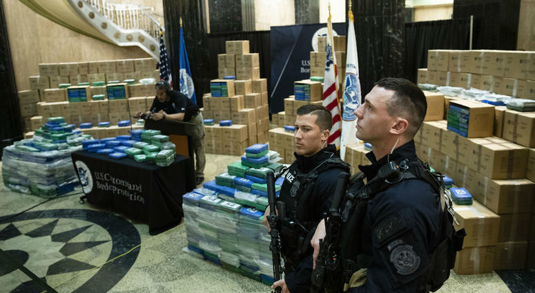 Officers stand guard over a fraction of the cocaine sized from a ship at a Philadelphia port is seen ahead of a news conference at the U.S. Custom House in Philadelphia, Friday, June 21, 2019.