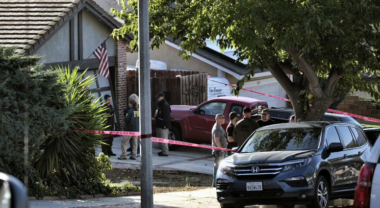 Ventura County Sheriff's deputies and FBI investigators stand outside the house of shooting suspect David Ian Long in Newbury Park, Calif., on Thursday, Nov. 8, 2018.