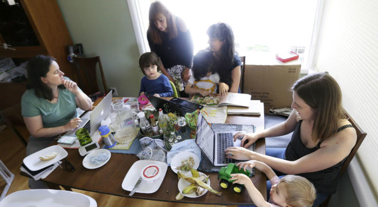 In this Wednesday, June 27, 2018, photo, a small group of stay-at-home mothers, with children at their sides, work to organize an immigration rally in Portland, Ore.
