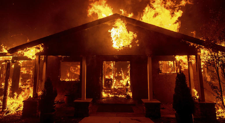 In this Thursday, Nov. 8, 2018 file photo, a home burns as the Camp Fire rages through Paradise, Calif.