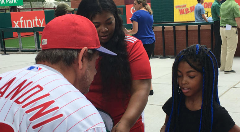 Former Phillies second baseman and coach Mickey Morandini, now a team ambassador, speaks with a youngster about the supplies she'll need for school this fall.