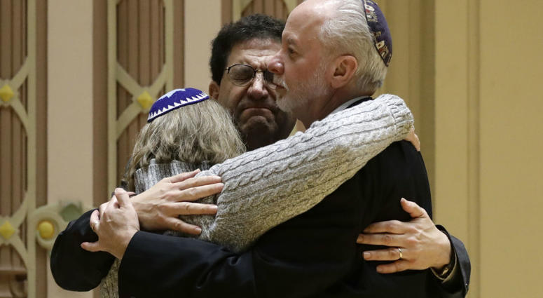 Rabbi Jeffrey Myers, right, of Tree of Life/Or L'Simcha Congregation hugs Rabbi Cheryl Klein, left, of Dor Hadash Congregation and Rabbi Jonathan Perlman during a community gathering held in the aftermath of a deadly shooting at the Tree of Life Synagogue