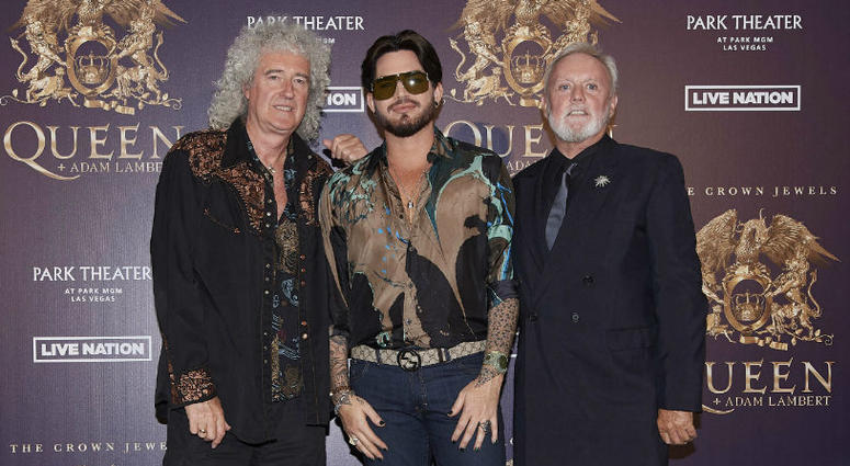 """In this Aug. 28, 2018, file photo, Brian May, from left, Adam Lambert, and Roger Taylor of Queen + Adam Lambert pose for a photo at the """"The Crown Jewels"""" residency press conference at the MGM Resorts aviation hanger in Las Vegas."""