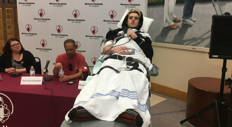 Ryan Straschnitzki speaks about his rehabilitation plan at Shriners Hospital Philadelphia. He is joined by Shriners Care Manager Kimberly Curran (left) and his father, Tom (center).