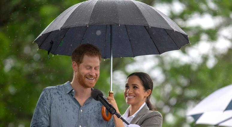 10/17/2018 - The Duchess of Sussex holds an umbrella as the Duke of Sussex makes a speech at a community picnic in Victoria Park in Dubbo, New South Wales, on the second day of the royal couple's visit to Australia.