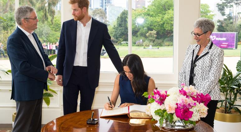 10/19/2018 - The Duke and Duchess of Sussex sign the visitor book at Government House, alongside Governor of Victoria Linda Dessau (right) and her husband Anthony Howard (left) at a reception given by the Governor of Victoria, at Government House.