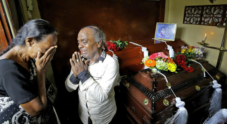 A Sri Lankan family mourns next to the coffins of their three family member, all victims of Easter Sunday bombing, in Colombo, Sri Lanka, Tuesday, April 23, 2019.