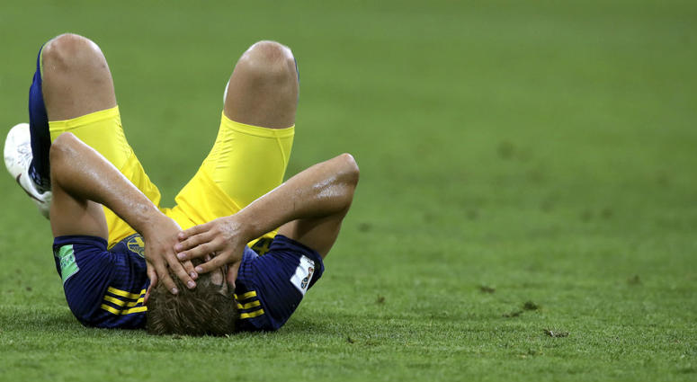 Sweden's Ludwig Augustinsson holds his head as he lies on the pitch at the end of the group F match between Germany and Sweden at the 2018 soccer World Cup in the Fisht Stadium in Sochi, Russia, Saturday, June 23, 2018. Germany won 2-1.