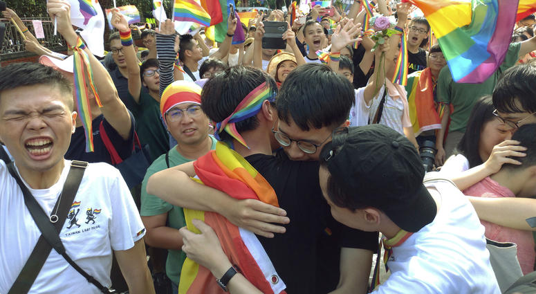 Same-sex marriage supporters hug outside the Legislative Yuan in Taipei, Taiwan, Friday, May 17, 2019, after Taiwan's legislature has passed a law allowing same-sex marriage in a first for Asia.