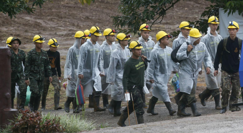 Rescuers walk toward the entrance to a cave complex where five were still trapped, in Mae Sai, Chiang Rai province, northern Thailand Tuesday, July 10, 2018. The eight boys were rescued from the flooded cave.