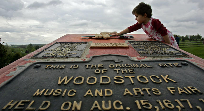 This May 15, 2008 file photo shows Emma Cenholt, 3, of Trumbull, Conn., playing on a memorial at the site of the Woodstock Music and Arts Fair in Bethel, N.Y.