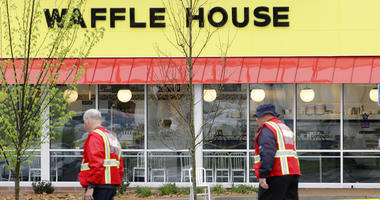A police car sits in front of a Waffle House restaurant.