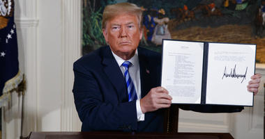 President Donald Trump shows a signed Presidential Memorandum after delivering a statement on the Iran nuclear deal from the Diplomatic Reception Room of the White House.