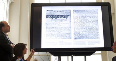 A video shows the text underneath two taped off pages from Anne Frank's diary during a press conference at The Anne Frank Foundation's office in Amsterdam.