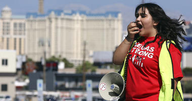 Volunteer Jenifer Murias yells into a megaphone as Culinary Union members file into a university arena to vote on whether to authorize a strike.