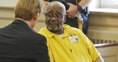 Attorney Matthew Reisig speaks with his client Hudy Muldrow before the start of the detention hearing.