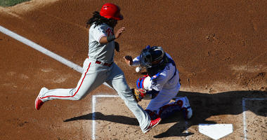 Philadelphia Phillies' Maikel Franco, right, scores on a single by Jorge Alfaro as Los Angeles Dodgers catcher Yasmani Grandal misses the throw during the second inning.