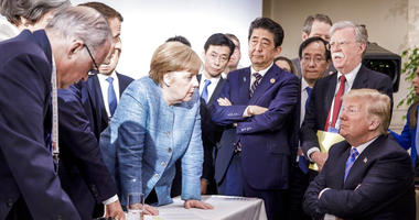 In this photo made available by the German Federal Government, German Chancellor Angela Merkel, center, speaks with U.S. President Donald Trump, seated at right, during the G7 Leaders Summit in La Malbaie, Quebec, Canada.