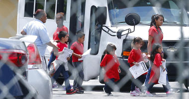 In this June 21, 2018, photo, migrant children walk off a bus at the Catholic Charities' Msgr. Bryan Walsh Children's Village in Cutler Bay, Fla.