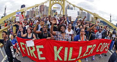 In this June 22, 2018, file photo, demonstrators protesting the fatal police shooting of Antwon Rose Jr. cross the Roberto Clemente Bridge during an evening rush hour march that began in downtown Pittsburgh.