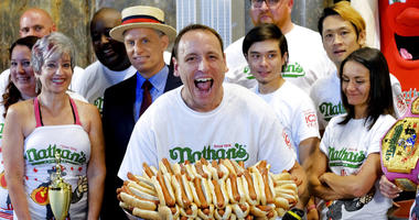 Ten-time and defending Nathan's Famous Men's Champion Joey Chestnut poses with 72 hot dogs during Nathan's Famous International Fourth of July Hot Dog Eating Contest weigh-in at the Empire State Building on Tuesday, July 3, 2018, in New York.